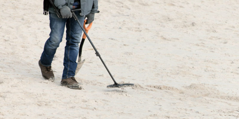 using metal detector and shovel at the beach