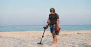 Guy using metal detector on beach sand